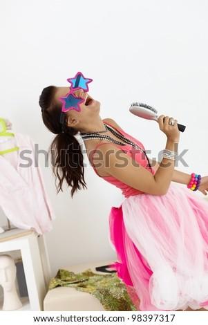 Young girl having fun at home, singing, posing, enjoying herself. - stock photo
