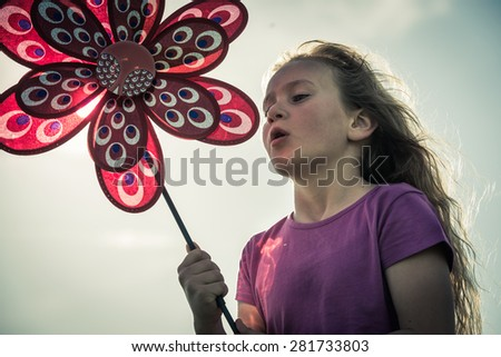 Young girl having fun with a pinwheel - stock photo