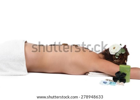 Young girl having hot stone therapy - stock photo