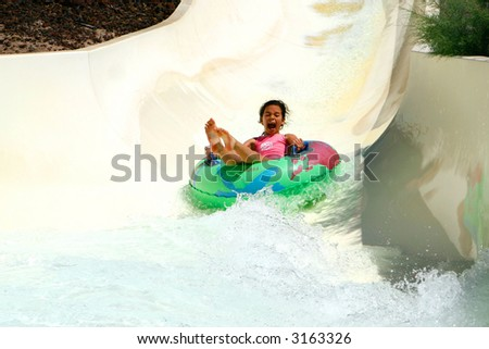 Young girl having lots of fun on rubber ring going down the water slide. - stock photo