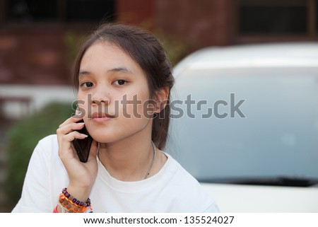 Young girl hold mobile phone in her hand with out focus background - stock photo