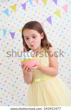 Young girl holding a birthday cake with cream on her nose - stock photo