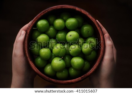 Young girl holding a bowl of green plums. Food, healthy eating and lifestyle concept - stock photo