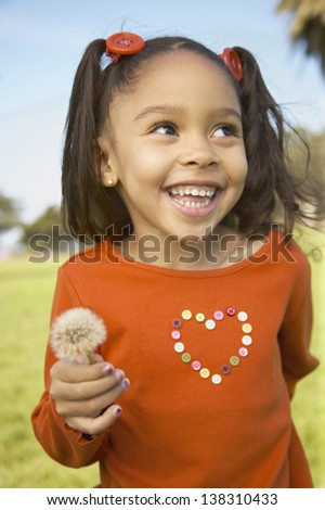 Young girl holding a dandelion (soft focus) - stock photo