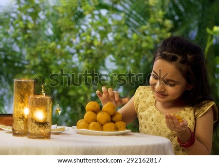 Young girl holding a laddoo - stock photo