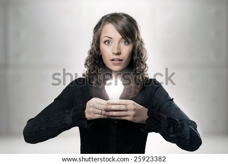 Young girl holding a light bulb - stock photo