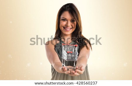 Young girl holding a supermarket cart toy - stock photo