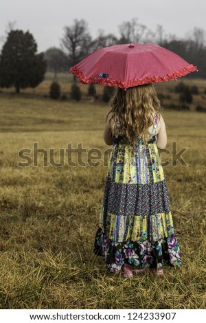 young girl holding an umbrella in the rain looking out at a field. Dreary day with rain. Pretty spring dress. Girl wanting to play, waiting for rain to stop. - stock photo