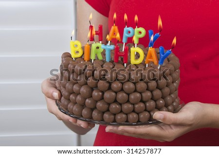 Young girl holding Chocolate Birthday Cake decorated with candy malt balls in front of her with happy birthday candles burning. Fast and easy home made cake for children or adult birthday party - stock photo
