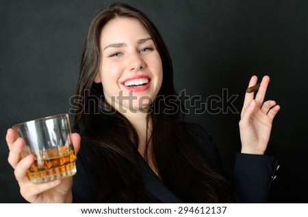 Young girl holding cigar and glass of whisky. Happy face expression, party style. - stock photo