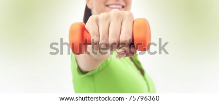 Young girl holding dumbbell, FOCUS ON HAND - stock photo