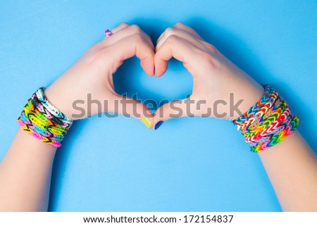 Young girl holding hands in a heart shape, wearing loom bracelets. Close up. Young fashion concept - stock photo