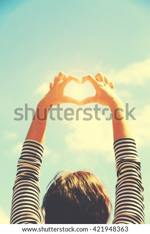 Young girl holding hands on blue sky background. Retro style - stock photo