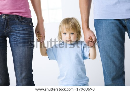 Young girl holding hands with parents. She's looking at camera. Focused on little girl. Front view. - stock photo