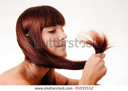 Young girl holding her hair tips - stock photo