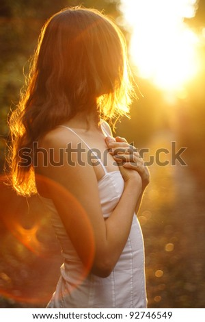 Young girl holding her hands on her heart looking towards the setting sun - stock photo