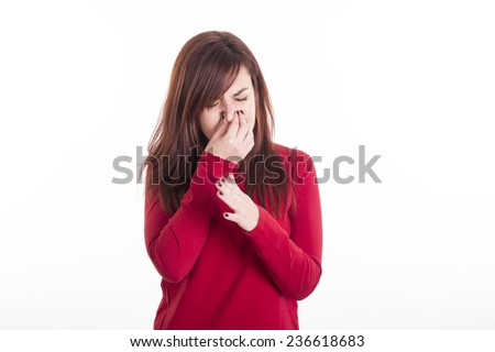 Young girl holding her nose smelling something stinking moving her hand - stock photo