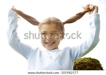 Young girl holding her ponytails up in the air with her hands, smiling naughtily. - stock photo
