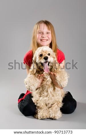 Young girl holding joyful curly spaniel - stock photo