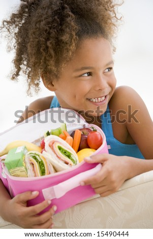 Young girl holding packed lunch in living room smiling - stock photo
