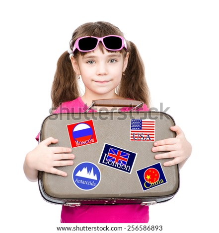 Young girl holding suitcase with stickers from various countries - stock photo