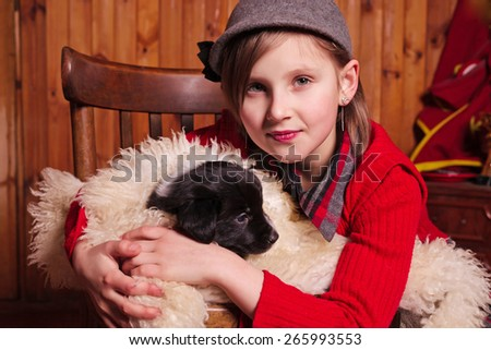 Young girl hugging a puppy wrapped in a sheepskin Farm - stock photo