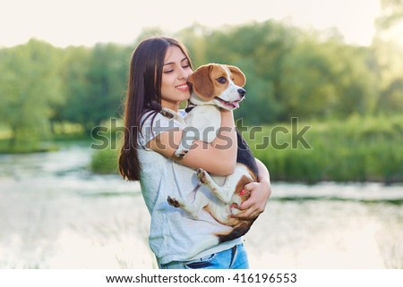 Young girl hugging her dog in the park. - stock photo