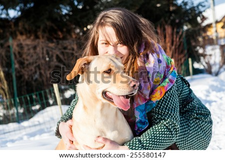 Young girl hugging her golden dog in snow - stock photo