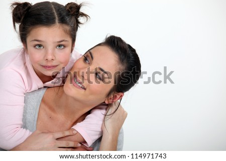 Young girl hugging her mother - stock photo
