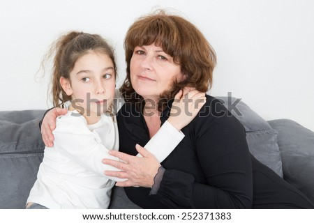young girl hugging her senior grand mother - stock photo