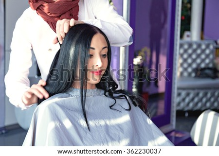 young girl in a beauty salon. Job hairdresser and stylist. A girl with long black hair in a barber chair. A gray cape. Purple background. Caucasian appearance. doing make-up - stock photo