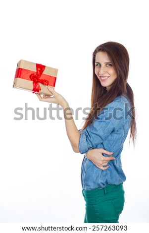 Young girl in a blue denim shirt and green jeans with gift box in hands. Beautiful brunette with long hair isolated on white background. Gift box of kraft paper with red ribbon - stock photo