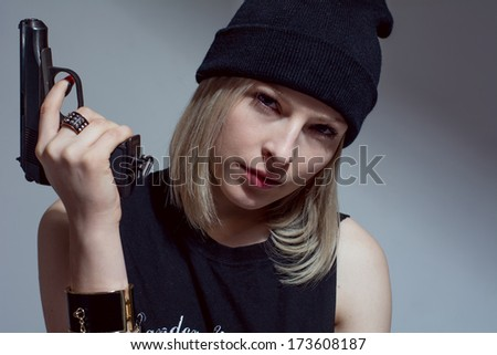 Young girl in a dark cap with a raised gun. Blonde with a gun - stock photo