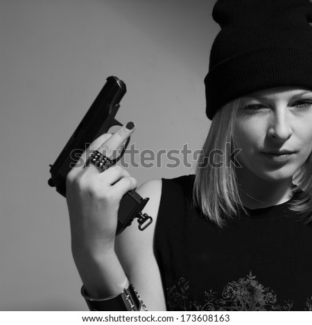 Young girl in a dark cap with a raised gun. Blonde with a gun. monochrome image - stock photo