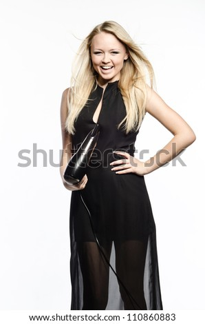 Young girl in a nice black  dress poses with hairdryer - stock photo