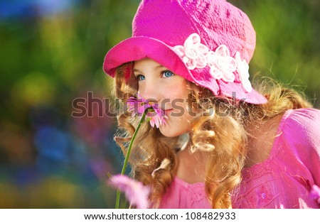 young girl in a pink jacket and pink hat smelling a flower in the garden - stock photo