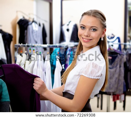 young girl in a shop buying clothes - stock photo