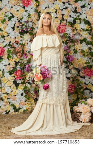 young girl in a spring garden of roses. - stock photo
