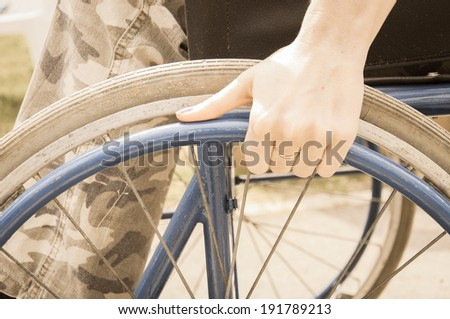 Young girl in a wheelchair alone to ride through in the park - stock photo