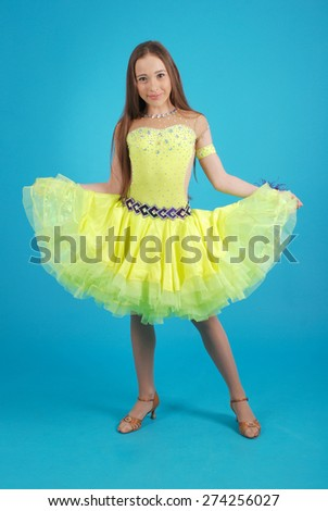 Young girl in ballroom dress on blue studio background. - stock photo