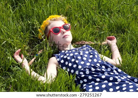 young girl in beautiful summer dress, sunglasses and dandelion garland lying on green grass closeup - stock photo