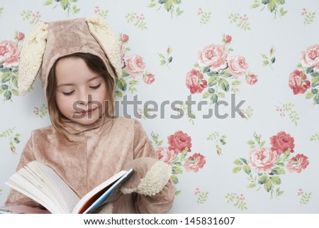 Young girl in bunny costume reading book against wallpaper with floral pattern - stock photo