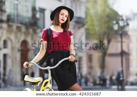 Young girl in burgundy shirt, black skirt and hat with bag. Standing near bicycle, looking at camera and smiling. Cycling, city, outdoor - stock photo