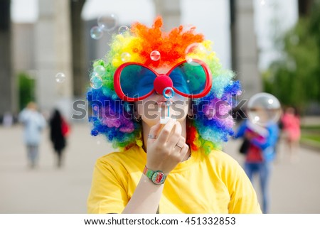 Young girl in clown costume blowing bubbles outdoors at summer day - stock photo