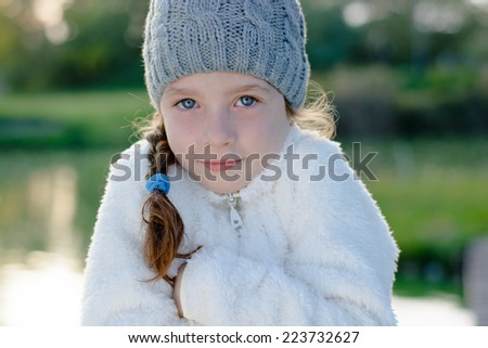 Young girl in cold weather, wearing warm clothes - stock photo