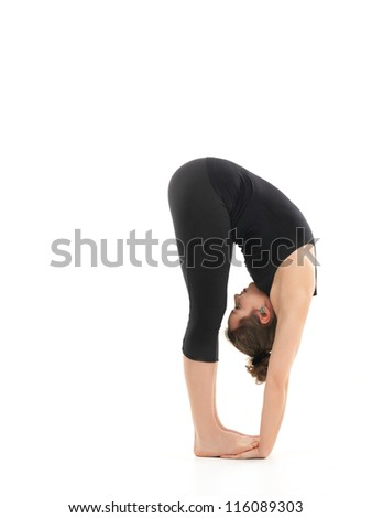 young girl in difficult forward bending yoga posture, dressed in black, on white background - stock photo
