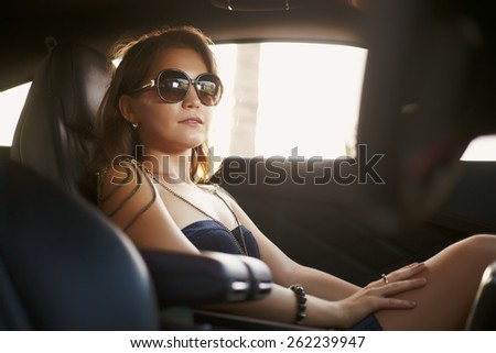 Young girl in dress in luxury motor car - stock photo