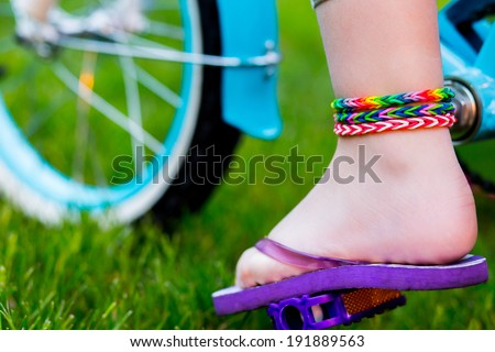 Young girl in flip-flops wearing loom bracelets on her hands and legs riding the bicycle. Close up. Young fashion concept - stock photo