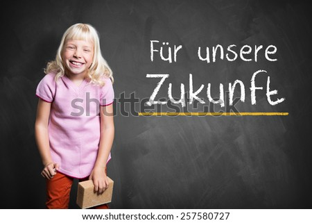 """young girl in front of a blackboard with the sentence """"For our future"""" in German - stock photo"""