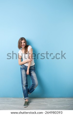 Young girl in full in a modern style on a background of a blue wall - stock photo